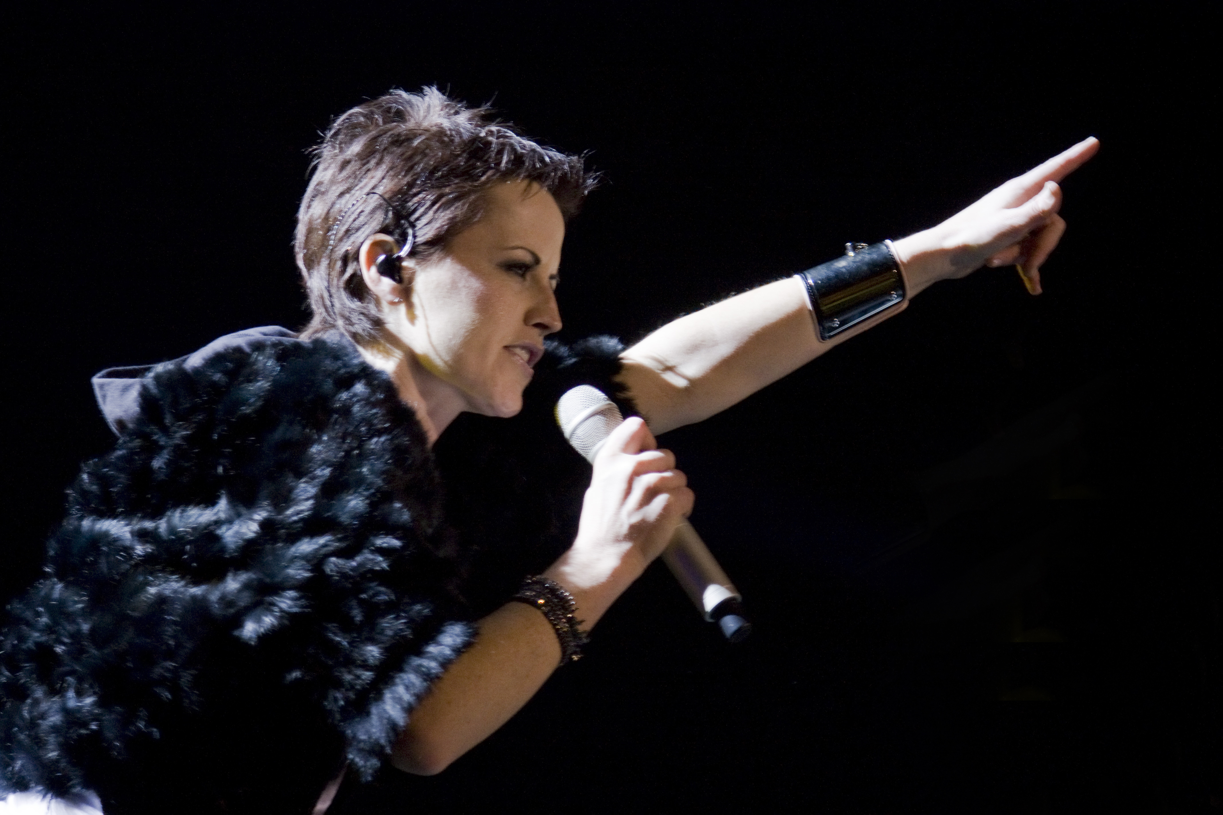 Delores O'Riordan with a microphone, pointing up, during a The Cranberries performance in Barcelona.