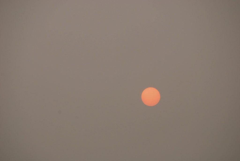 The sun as a sharp orange circle through the cover of smoke.