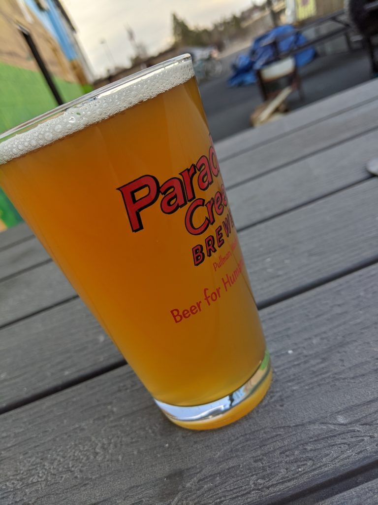 A pint of beer on a table outside in a pandemic.